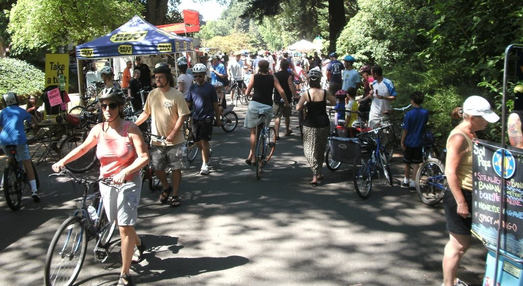 People walking, cycling, scooting, etc happily together as part of a street closure in Portland, Oregon.